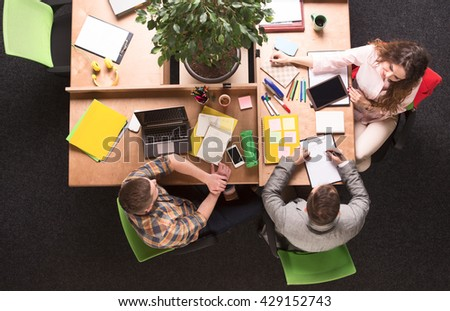 Top view of business people sitting in office. Busy and executive people working upon different business projects. - stock photo