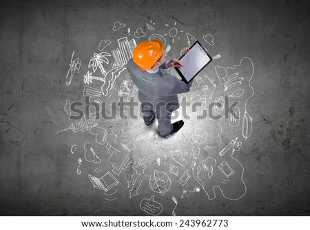 Top view of businessman and business sketches on floor - stock photo