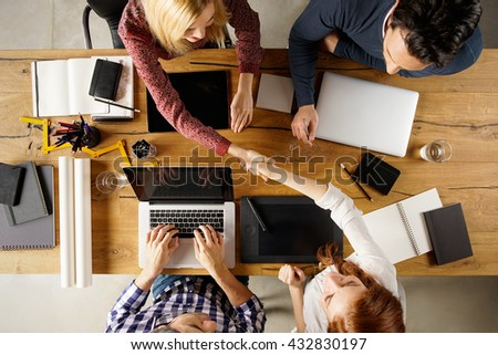 Top view of businesspeople shaking hands after sealing a deal. High angle view of casual businesswomen shaking hands after concluding business agreement. - stock photo