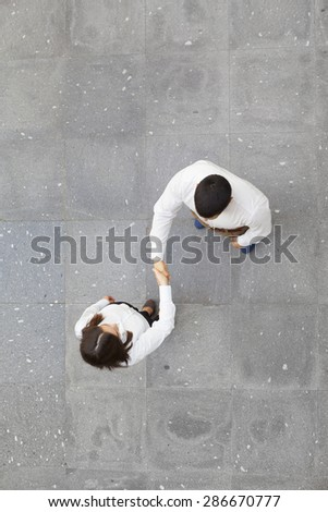 Top view of businesspeople shaking hands outdoors - stock photo