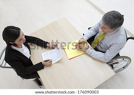 Top view of Businesswoman interviewing disabled candidate at desk in office  - stock photo