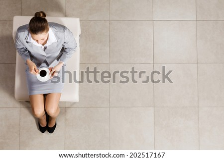 Top view of busineswoman sitting on chair with cup of coffee - stock photo