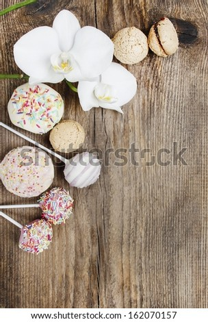 Top view of cake pops, muffins, cupcakes and macarons on wooden table. - stock photo