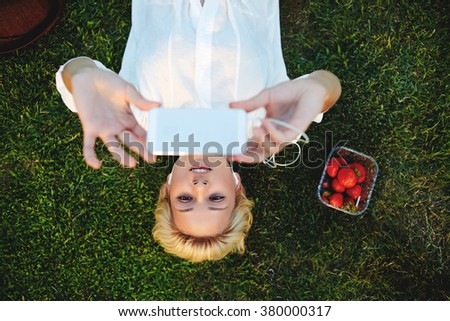 Top view of charming female photographing herself on mobile phone while lying down on green grass in the park, pretty hipster girl in headphones taking photo via cell telephone for social network - stock photo