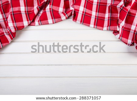 Top view of checkered kitchen towels on wooden table. Free space for your creative information - stock photo