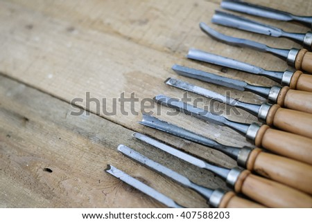 Top view of chisel tools set on wooden surface, closeup flat lay picture - stock photo