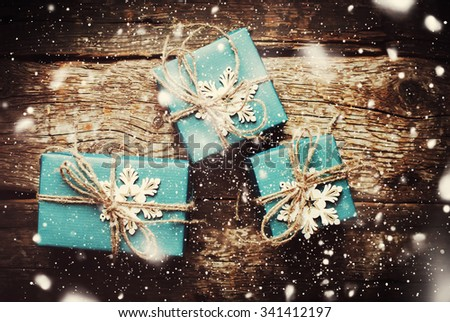 Top View of Christmas Boxes in Blue Paper Decorated with Snowflakes, Linen Cord on Wooden Table. Drawn Snow. Dark toned - stock photo