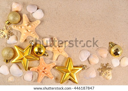 Top view of Christmas decorations and seashells and starfish on a beach sand  - stock photo