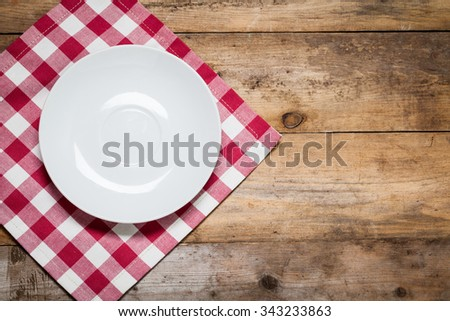Top view of clean empty plate on wooden tabletop with napkin - stock photo