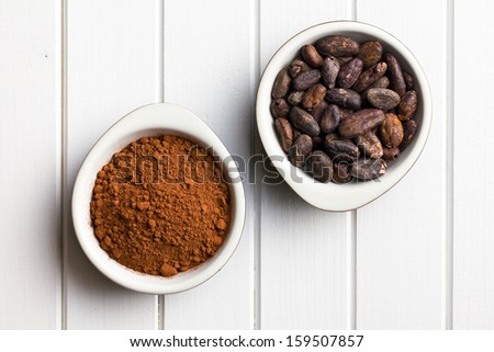 top view of cocoa beans and cocoa powder in bowls - stock photo