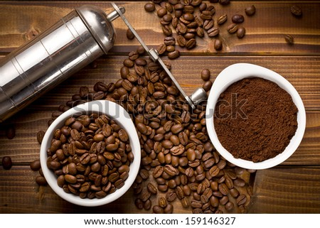 top view of coffee beans with ground coffee and grinder - stock photo