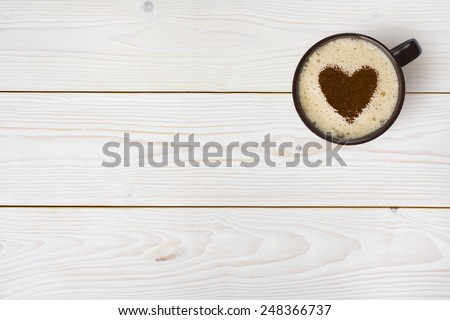 Top view of coffee cup with heart on wooden background - stock photo