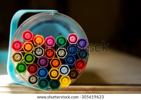 Top view of colored pens in box with dark tone and selective focus  - stock photo
