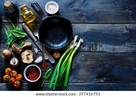 Top view of colorful organic vegetables and seasoning ingredients on rustic kitchen table with olive oil and balsamic vinegar. Healthy food or vegetarian food concept. - stock photo