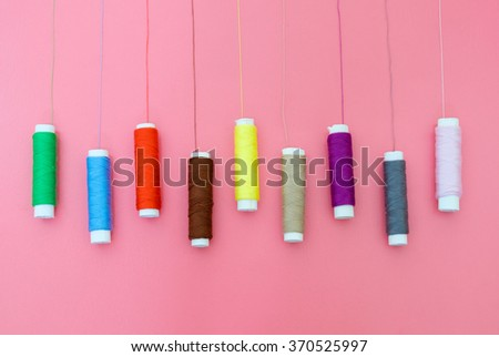 Top view of colorful thread spools on pink background - stock photo