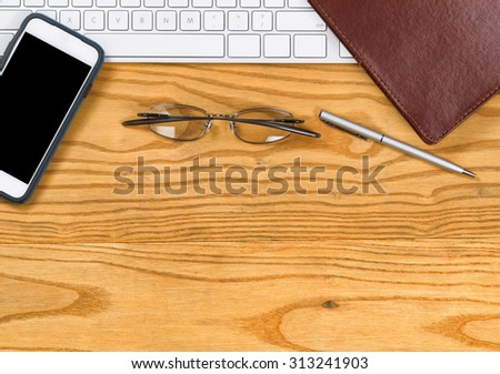 Top view of computer keyboard notepad binder, reading glasses, pen and cell phone on desktop.  - stock photo