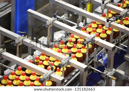 Top view of conveyor with bottles with fresh light beer in modern beer factory. - stock photo