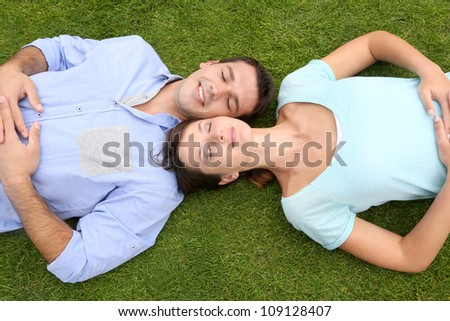 Top view of couple relaxing with eyes shut in grass - stock photo