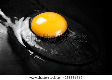 Top View of Cracked Raw Egg with Bright Yellow Yolk on Smooth Black Surface Such as Frying Pan or Counter - stock photo
