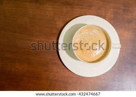 Top view of cup of hot coffee latte on wood table - stock photo