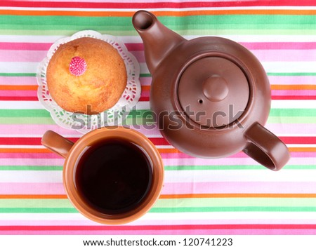 Top view of cup of tea and teapot on colorful tablecloths - stock photo
