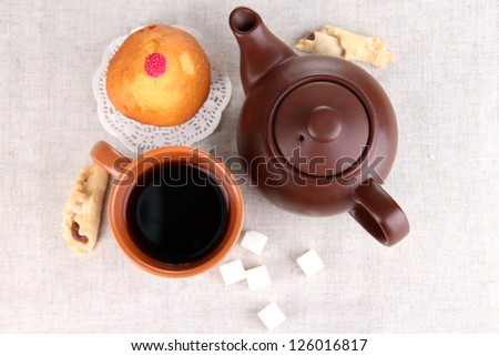Top view of cup of tea and teapot on linen tablecloths - stock photo
