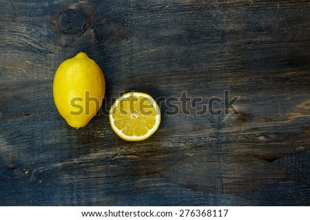 Top view of cut half and whole lemons on dark rustic boards. Background with space for text. - stock photo
