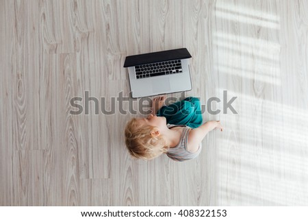 Top view of cute child using laptop at home - stock photo