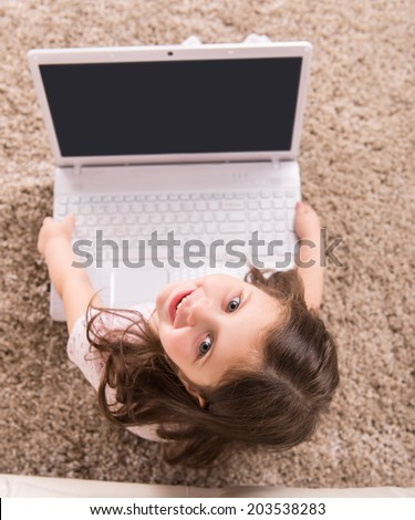 top view of cute girl holding computer. nice girl sitting on floor and smiling - stock photo