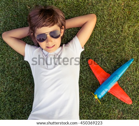 Top view of cute little boy in sun glasses looking at camera and smiling while lying with hands behind head on the grass, toy airplane is near - stock photo