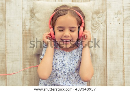 Top view of cute little girl in headphones listening to music with closed eyes and smiling while lying on wooden floor - stock photo