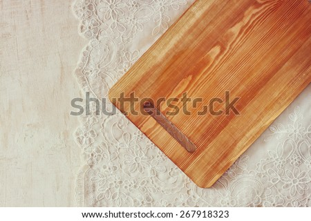 top view of Cutting board on wooden table over vintage lace table cloth and wooden table. room for text  - stock photo