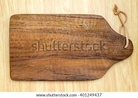 Top view of dark brown wooden chopping block on light wood counter,Kitchenware. - stock photo