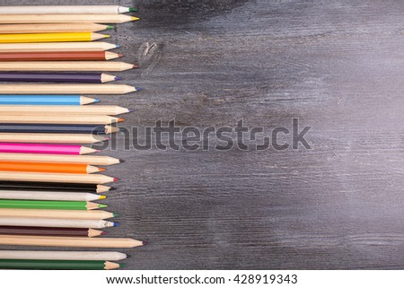 Top view of dark wooden desktop with row of colorful pencils. Mock up - stock photo