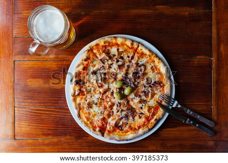 Top view of delicious Pancetta Cipolla Pizza and Beer Mug on wooden table. Ingredients peeled tomato, cheese, bacon, onion, olives, oregano. - stock photo