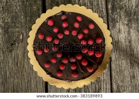 Top view of delicious whole chocolate cake decorated with fresh ripe raspberries on a golden plate placed on textured rustic wooden desk. - stock photo