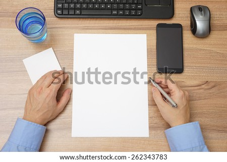 top view of desk with empty paper and man with pen in hand, ready for sample text - stock photo