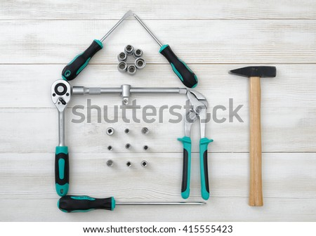 Top view of different type of constructive tools making shape of home, house. Construction instruments and tools. Set of tools. Compact tool box. Mend and repair. Home tool kit. - stock photo