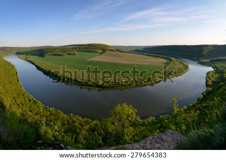 Top view of Dnestr (Dniester) river in springtime. The river surrounds multicoloured field. Mountains slopes are covered with lush bright green  vegetation. - stock photo