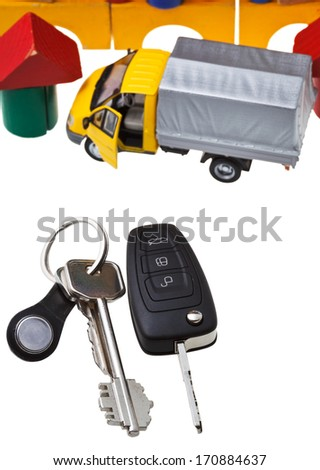 top view of door keys, vehicle key, new truck model and wooden block toy house isolated on white background - stock photo