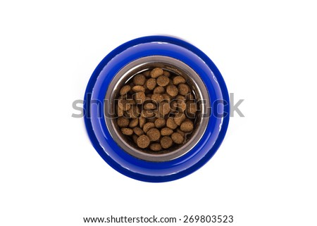 Top view of dry dog food in blue bowl, isolated on white background. - stock photo