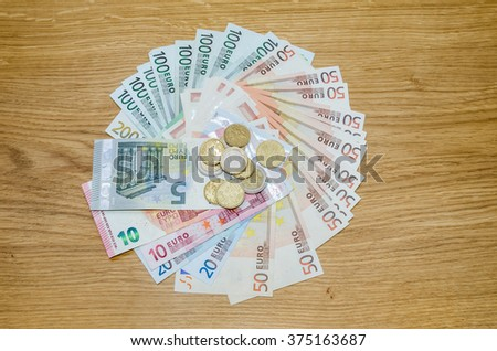 Top view of Euro coins and banknotes  on wooden table - stock photo