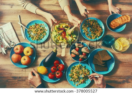 Top view of family having dinner together sitting at the rustic wooden table. Enjoying  family dinner together. - stock photo