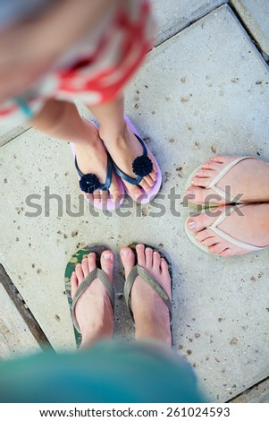Top view of family mother and kids feet in flip flops on summer vacation - stock photo