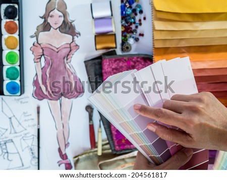 Top view of fashion designer working with pantone palette sample and hand-drawn illustration - stock photo