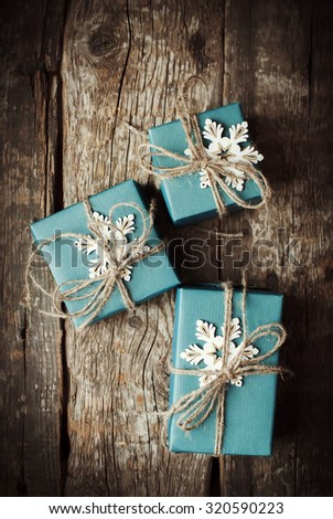 Top View of Festive Boxes in Blue Paper Decorated with Snowflakes and Linen Cord on Wooden Table - stock photo