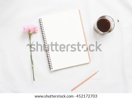 Top view of flower and  blank notebook on white fabric workspace background. - stock photo