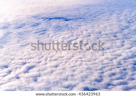 Top view of fluffy cloud sky view from flying airplane window - stock photo