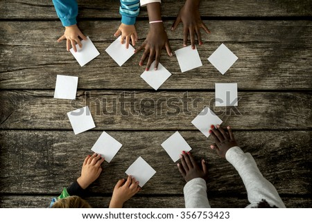 Top view of four children of mixed races assembling a heart shape of white cards over a textured rustic wooden boards. - stock photo