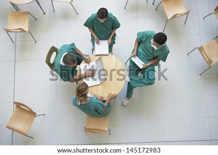 Top view of four physicians in meeting with reports and laptop at the cafeteria - stock photo